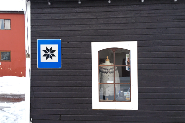 An Icelandic Lopapeysa in a shop window in Skagafjörður - the road sign is a countrywide road sign symbol used to indicate where to find handmade items.