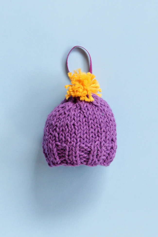 Get a free pattern for this mini knit beanie, which works great for holiday ornaments or as a gift topper!