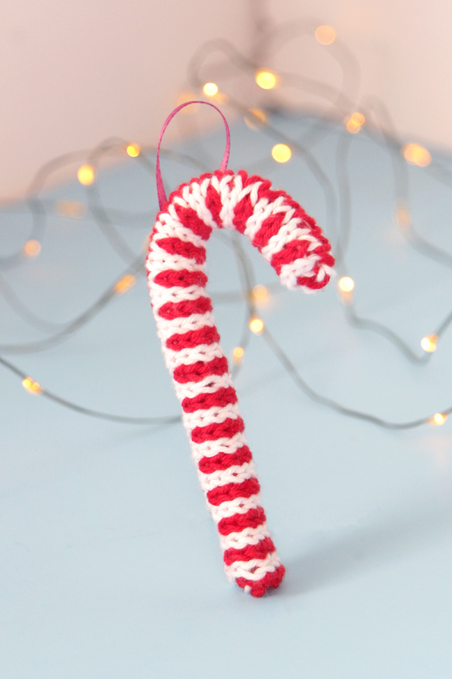 Trim your tree with this free candy cane ornament knitting pattern! Knit flat and seamed, you can quickly make this keepsake ornament with yarn scraps and pipe cleaners.